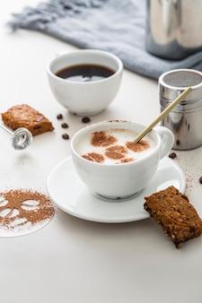 Hoge hoek van koffiekopjes met desserts en bord