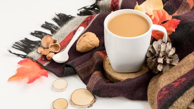 Hoge hoek van koffiemok met dennenappels en herfstbladeren