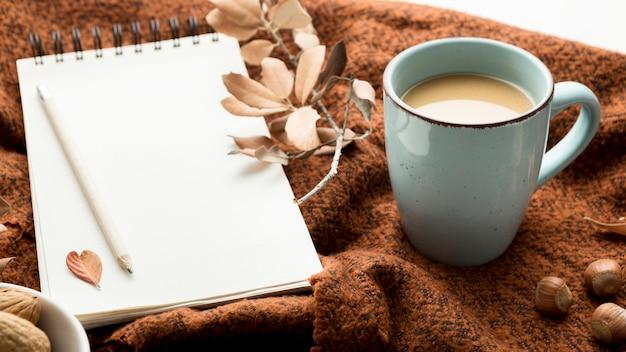 Hoge hoek van koffiemok met herfstbladeren en notitieboekje