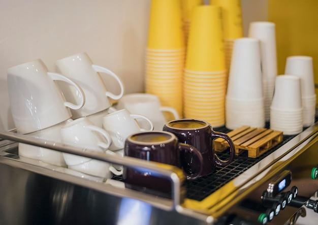 Hoge hoek van koffiezetapparaat en kopjes