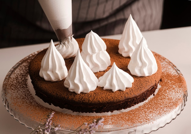 Hoge hoek van kok versieren cake met suikerglazuur