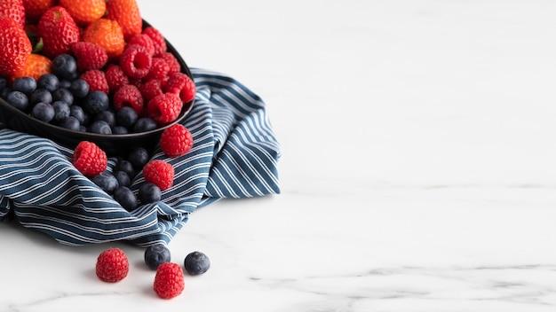Hoge hoek van kom met aardbeien, frambozen en bosbessen