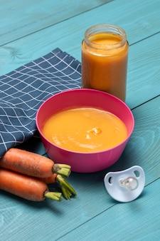 Hoge hoek van kom met babyvoeding en wortelen