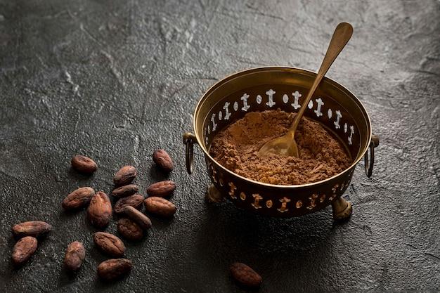 Hoge hoek van kom met cacaopoeder en cacaobonen
