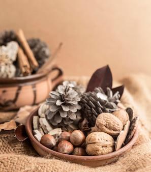Hoge hoek van kom met denneappels en noten op jute