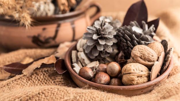 Hoge hoek van kom met noten en dennenappels op jute