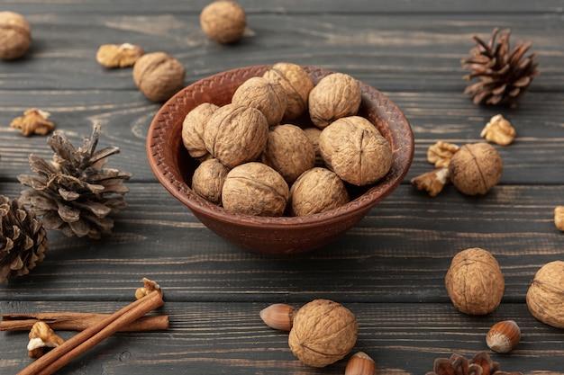 Hoge hoek van kom met walnoten en dennenappels