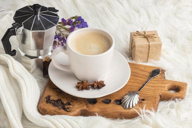 Hoge hoek van kopje koffie met aanwezig en waterkoker