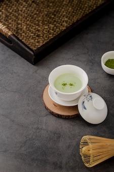 Hoge hoek van kopje matcha-thee met dienblad