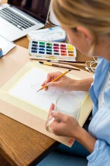 Hoge hoek van kunstenaar die op papier trekt