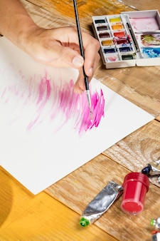 Hoge hoek van kunstenaar met verfborstel het schilderen in studio