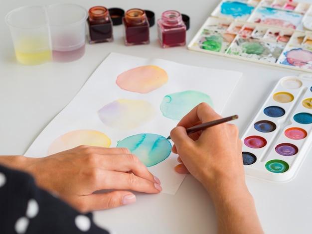 Hoge hoek van kunstenaar schilderen met aquarel en penseel