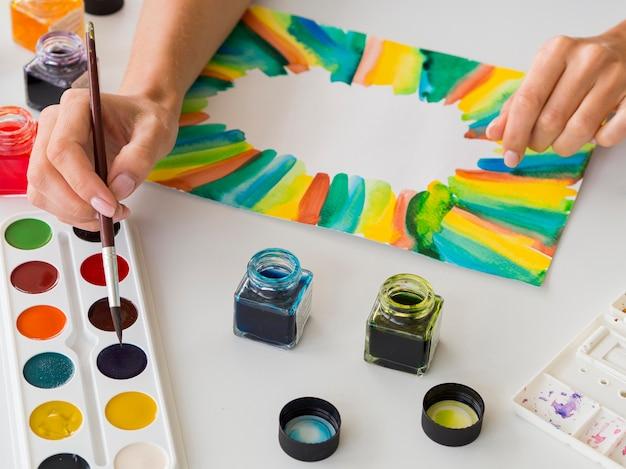 Hoge hoek van kunstenaar schilderen met aquarel