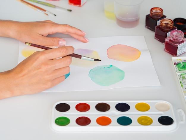 Hoge hoek van kunstenaar schilderen met behulp van aquarel