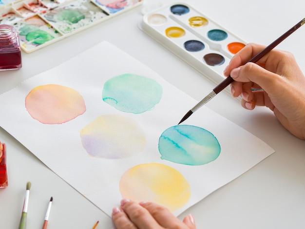 Hoge hoek van kunstenaar schilderen met penseel en aquarel