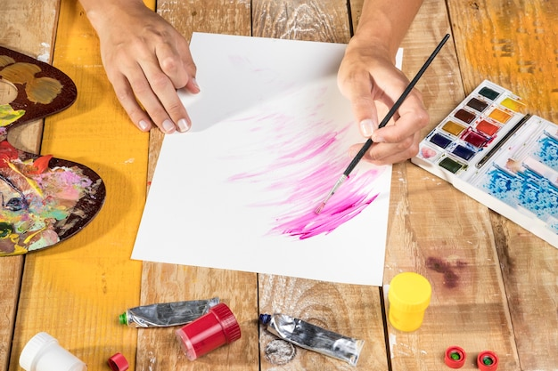 Hoge hoek van kunstenaar schilderen op papier