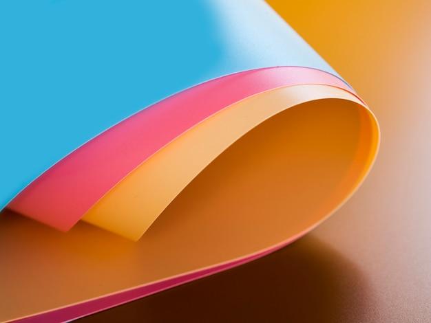 Hoge hoek van levendige kleurrijke gebogen papiervellen