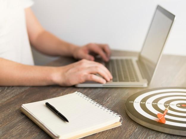 Hoge hoek van man aan het werk op laptop met dart en bord naast hem