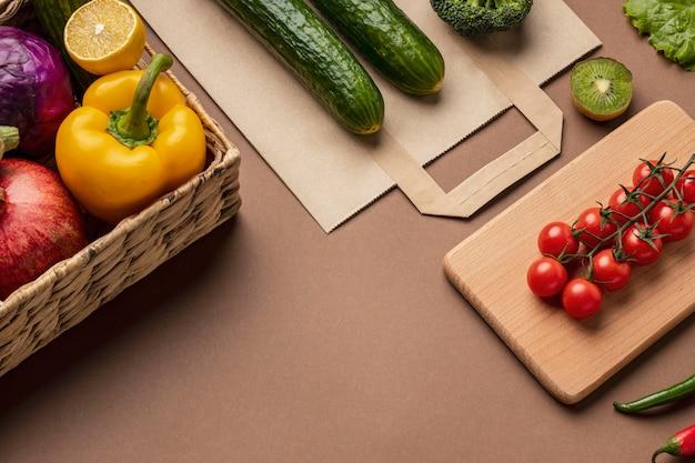 Hoge hoek van mand met biologische groenten met boodschappentas