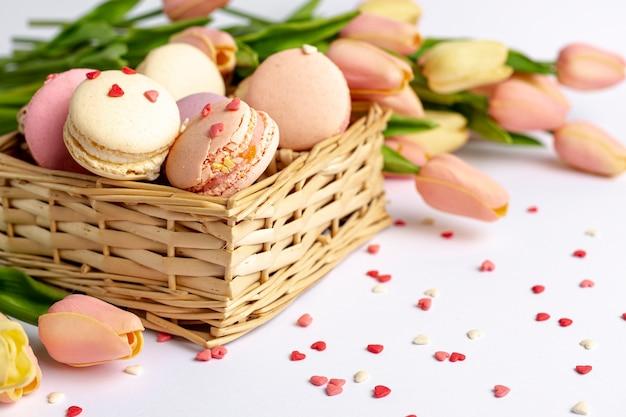 Hoge hoek van mand met macarons en tulpen voor valentijnsdag