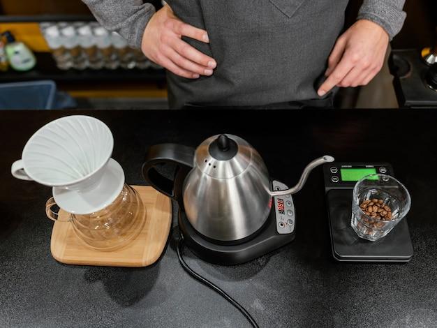 Hoge hoek van mannelijke barista die koffie met ketel en filter voorbereidt