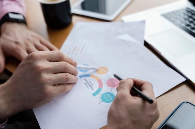 Hoge hoek van mannelijke collega's die grafiek op het werk analyseren