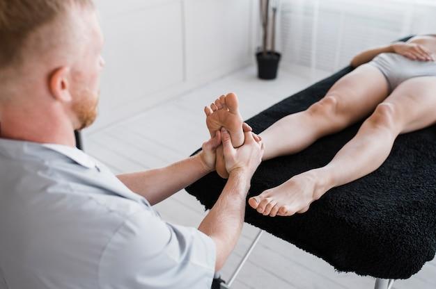 Hoge hoek van mannelijke fysiotherapeut met vrouwelijke patiënt