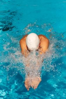 Hoge hoek van mannelijke zwemmer die in het zwembad zwemt