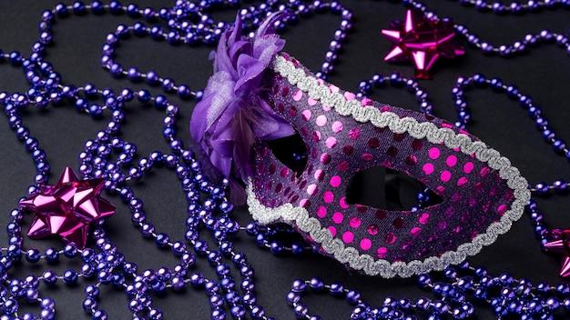 Hoge hoek van masker voor carnaval met veren en kralen