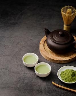 Hoge hoek van match theekopjes met theepot en kopie ruimte