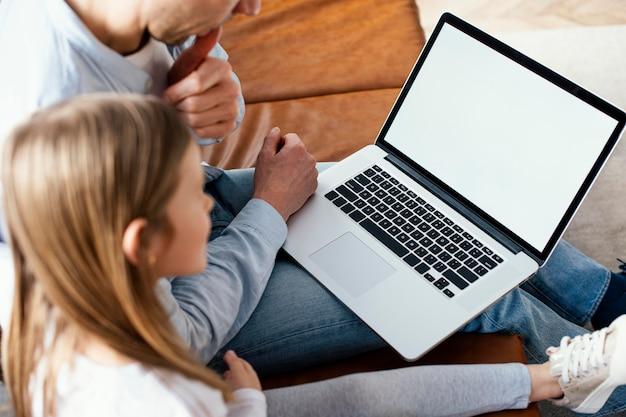Hoge hoek van meisje en haar vader tijd doorbrengen op laptop