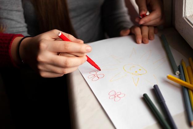 Hoge hoek van meisje met down syndroom en vrouw tekenen