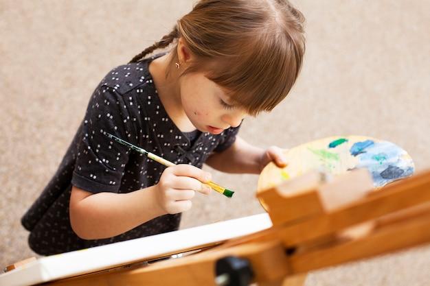 Hoge hoek van meisje met het syndroom van down schilderen