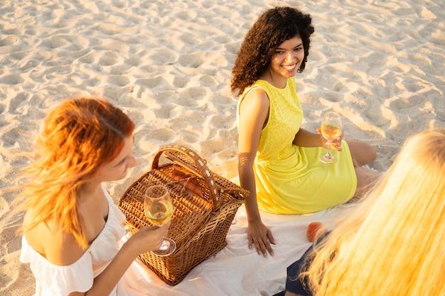 Hoge hoek van meisjes met een picknick op het strand