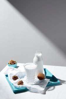 Hoge hoek van melkglas en fles met walnoten en exemplaarruimte