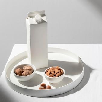 Hoge hoek van melkpak op dienblad met amandelen en walnoten