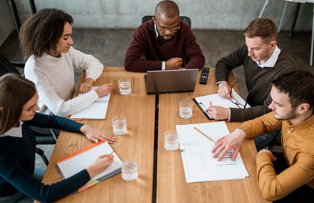 Hoge hoek van mensen aan tafel op kantoor tijdens een vergadering