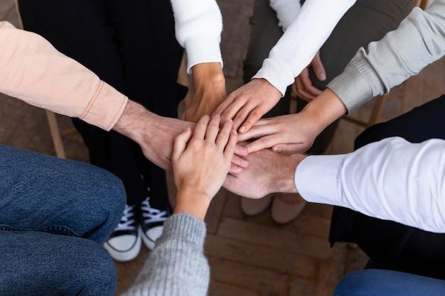 Hoge hoek van mensen die handen verenigen tijdens een groepstherapie-sessie