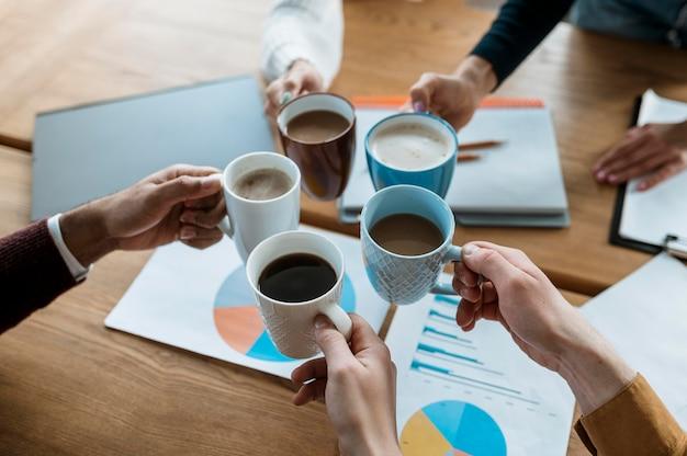 Hoge hoek van mensen juichen met koffiemokken tijdens kantoorvergadering