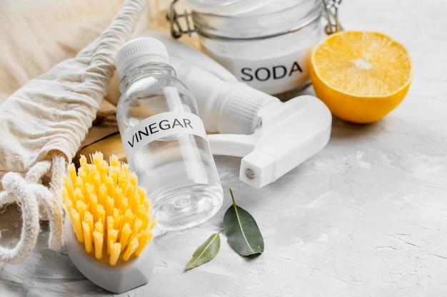 Hoge hoek van milieuvriendelijke schoonmaakborstels met azijn en citroen