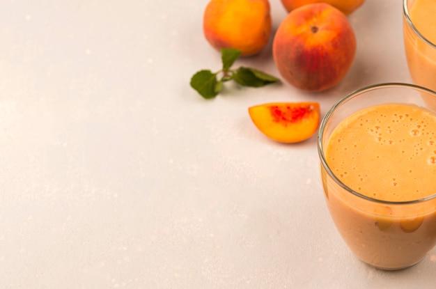 Hoge hoek van milkshakeglas met perziken en exemplaarruimte