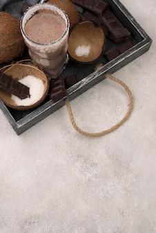 Hoge hoek van milkshakeglas op dienblad met kokosnoot en exemplaarruimte
