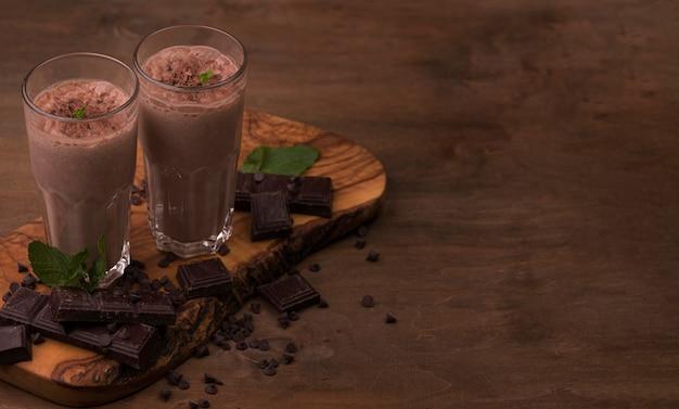 Hoge hoek van milkshakeglazen met exemplaarruimte en chocolade