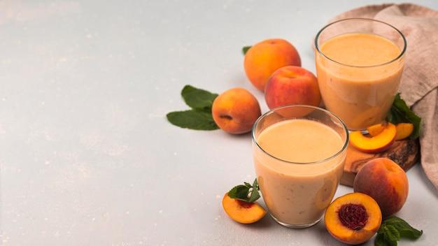 Hoge hoek van milkshakeglazen met perziken en exemplaarruimte