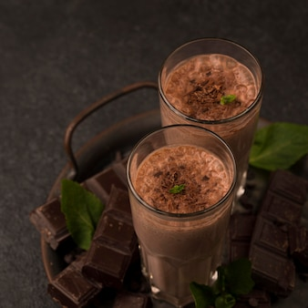 Hoge hoek van milkshakeglazen op dienblad met munt en chocolade