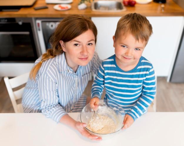 Hoge hoek van moeder en zoon koken
