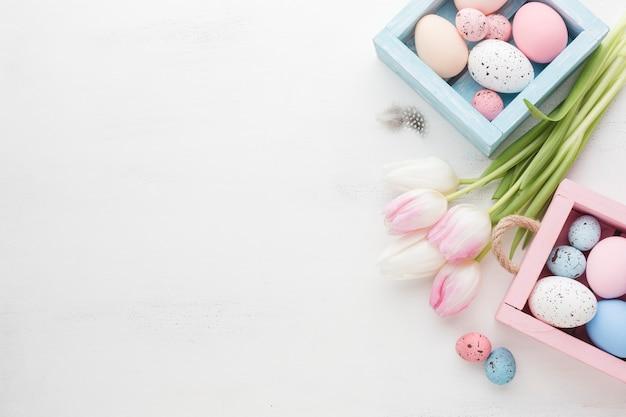 Hoge hoek van mooie tulpen met kleurrijke paaseieren