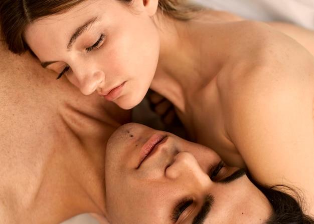 Hoge hoek van mooie vrouw en shirtless man in bed