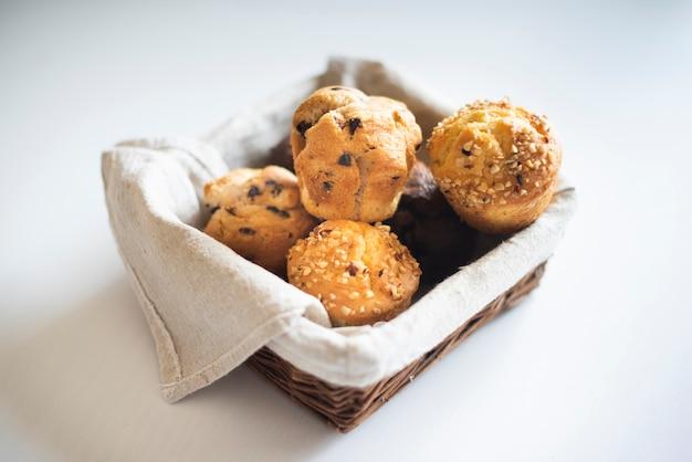 Hoge hoek van muffins in mand op effen achtergrond