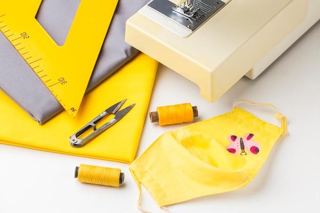 Hoge hoek van naaimachine met stof en gezichtsmasker